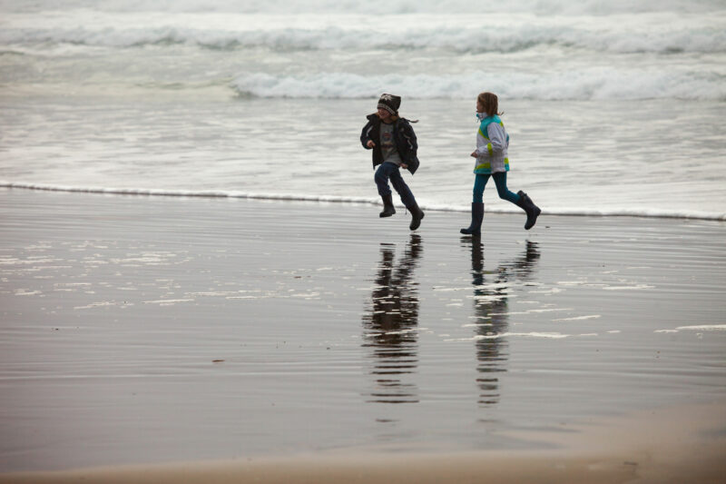Kids running from the winter waves